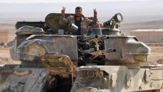 """A soldier from the Syrian government forces flashes the """"V"""" for victory sign in the eastern Syrian city of Deir Ezzor during an operation against Islamic State (IS) group jihadists on November 2, 2017."""