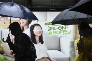 People walk past an advertisement as they take part in a rainy protest march from the Tsim Sha Tsui district of Hong Kong on October 6, 2019. - A Hong Kong judge on October 6 rejected a challenge to an emergency law criminalising protesters wearing face masks as democracy activists hit the streets again in defiance of the ban despite half the city's subway stations remaining closed.