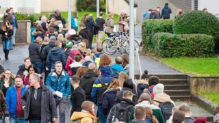 University students queue for a new email password