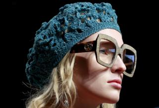 Gucci model's head - wearing large glasses and a woollen hat
