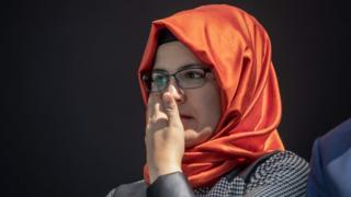 Hatice Cengiz, wearing an orange hijab and glasses, dries her eyes at a vigil for her late fiance Jamal Khashoggi, at the site of his murder in Istanbul