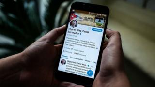 A person holds a smartphone showing the twitter account of Cuban President Miguel Diaz-Canel, in Havana, on October 10, 2018