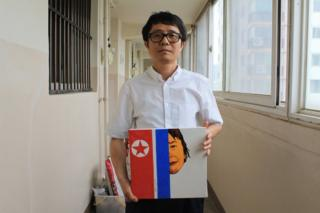 Song Byeok holds up one of his North Korean propaganda pieces