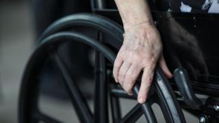 unidentified person holding wheelchair wheel
