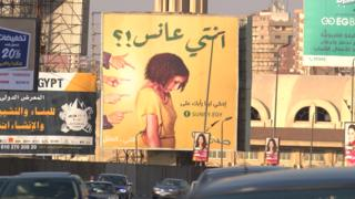 The billboard with a young woman being pointed at, which asks: Are you a spinster?