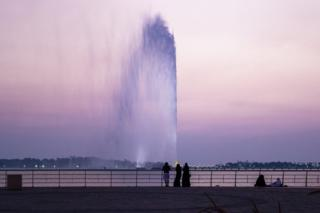 People looking at King Fahd's Fountain as the sun sets