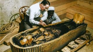 Arqueólogo Howard Carter e um trabalhador egípcio examinam um caixão feito de ouro maciço dentro da tumba
