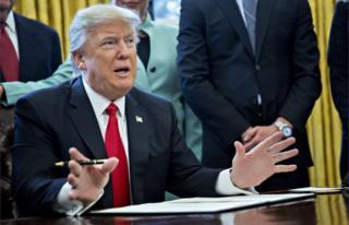 El presidente Donald Trump firma una orden ejecutiva.