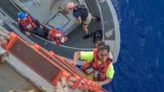 Una mujer subiendo por un barco