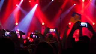 People with their arms up watching a music stage through their phones,