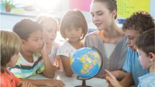 Children and teacher look at globe