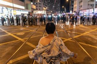 A pro-democracy protester wearing a Japanese bath gown stands in front of police cordon outside Tai Koo MTR station in Hong Kong