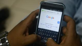 An Indian man using Google search on his mobile
