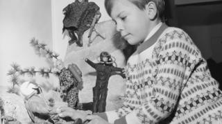 Boy playing with a display of Action Man toys