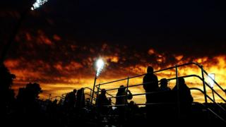 Cricket fans in a stand at Manuka Oval observe the sunset.