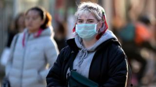 A woman wearing a facemask in Cardiff city centre