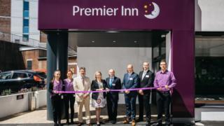 Guests at the official opening holding a ribbon across the front door of the Premier Inn