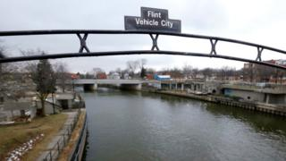 The file photo shows a sign over the Flint River noting Flint, Mich., as Vehicle City.