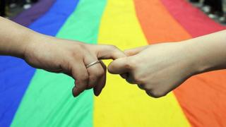 Hands being held in front of giant rainbow flag, Hong Kong