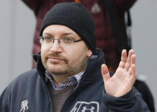 Journalist Jason Rezaian waves as he poses for journalists in front of Landstuhl Regional Medical Center in Landstuhl, Germany on 20 January, 2016 after being released from prison in Iran