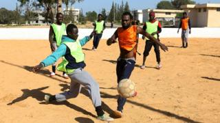 Cameroonian (orange) and Senegalese (yellow) African migrants, split into two teams, take part in a football match at the Libyan Interior Ministry's illegal immigration shelter in Tajoura,