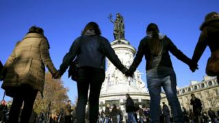 People hold hands near the Bataclan concert hall