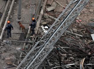 Bombeiros e cão farejador nos escombros do prédio