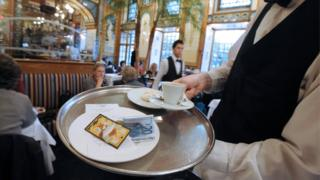 A waiter brings a coffee and the bill to clients at a restaurant in Nantes