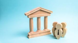Objetos de madeira representam um prédio governamental e três bonequinhos engravatados