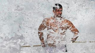 A swimmer at the Bronte ocean pool is hit by waves as large seas pound the coast at Bronte Beach in Sydney on March 6, 2017