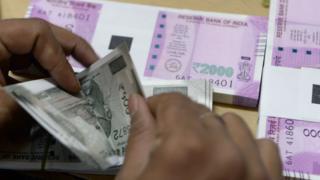 A man counts rupee notes