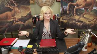 The character of Leslie Knope at her desk in Parks and Recreation