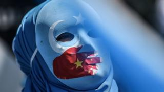 A pro-Uighur protester wears a mask painted with the colours of the East Turkestan flag and the Chinese flag