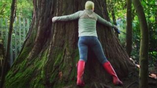 A woman hugging the redwood tree