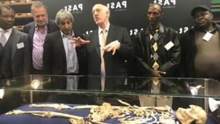 Le professeur Ron Clarke, au centre, dévoile le fossile de Little Foot à l'université de Witwatersrand de Johannesburg.