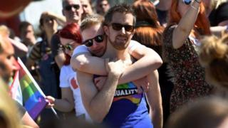 Two men embrace at a celebration in Sydney