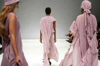 Models dressed in dusky rose-coloured clothes walk the runway at the Amanda Laird Cherry Show on the first day of South Africa Fashion Week, 3 April 2019, in Sandton, South Africa (composite image)
