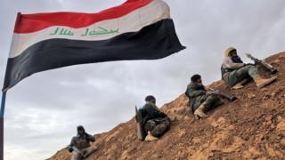 Hombres armados junto a una bandera del Estado Islámico