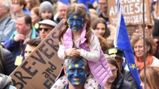 Child shown with EU flag painted on their face at the protest march
