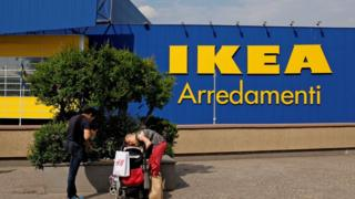 A family stop in front of an Ikea shop in a shopping park in Rome, Italy on 19 May 2017.