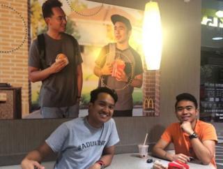 Jevh e Christian ao lado do pôster que fabricaram e penduraram no McDonald's