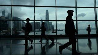 People walking past a blue-stained glass panel in front of the city skyline in Hong Kong