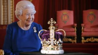 Queen Elizabeth II sitting next to the Imperial State Crown