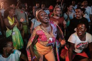 People dance and sing next to Ugandan singer Jackie Akello (C) during the 16th International African music festival 'Sauti za Busara' at the Old Fort in Stone town, Zanzibar, on 8 February 2019.