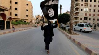 A member loyal to the Islamic State group waves an ISIL flag in Raqqa (29 June 2014)