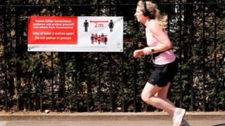science A runner running past a poster about social distancing