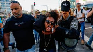 Members of the Israeli security forces detain a protester during a demonstration in Tel Aviv on July 3, 2019, against police violence and the recent killing of a young man. - Israel braced for a third day of protests after an off-duty police officer killed a young man of Ethiopian origin, as Israeli leaders urged calm amid accusations of racism. In areas throughout the country since July 1, protesters have blocked roads, burned tyres and denounced what they see as discrimination against the Ethiopian-Israeli community. Police say 136 people have been arrested and 111 officers have been wounded, many injured by stones, bottles and petrol bombs thrown at them.