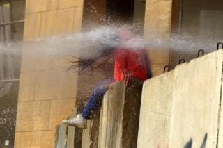 A Lebanese protester is hit with a burst from a water cannon