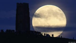 A full moon rises behind Glastonbury Tor as people gather to celebrate the summer solstice