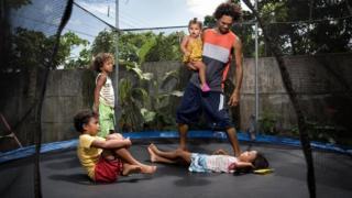 Pai brincando em pula-pula com filhos pequenos
